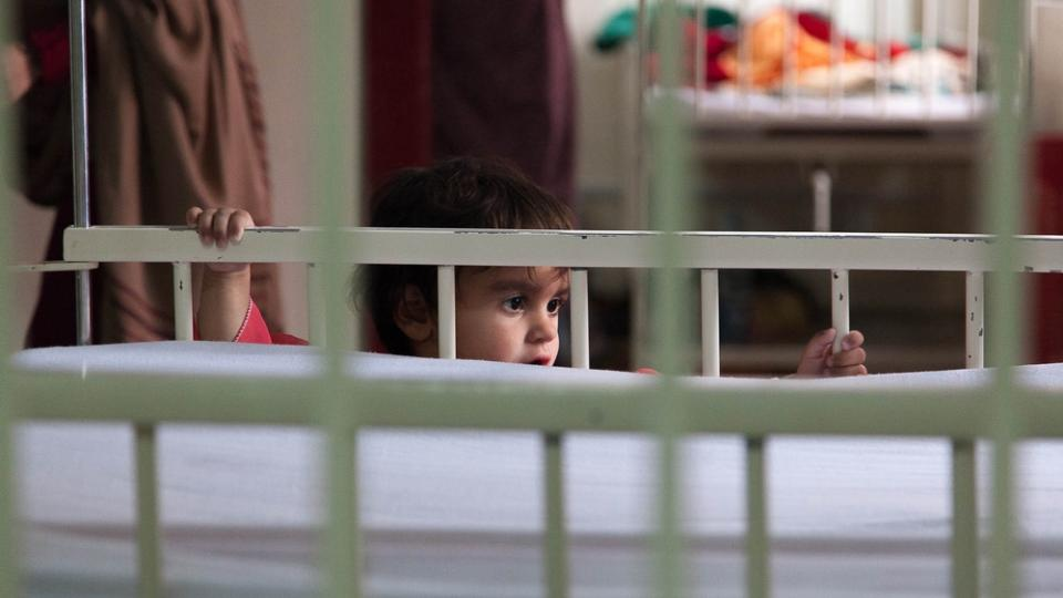 A small girl holds onto the side of a bed in Quetta, Pakistan