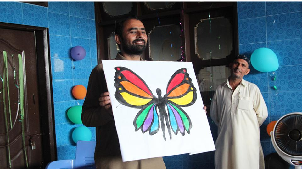 Health Promotion Supervisor TasawwarAli discusses the stigma of hepatitis C through the visual representation of a butterfly in Machar Colony, Pakistan.