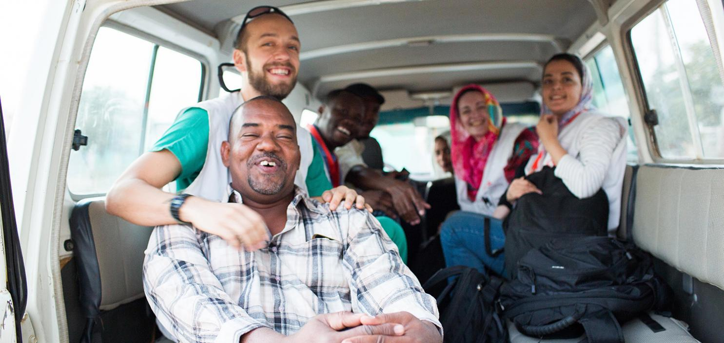 An MSF team laugh together in the back of a Land Cruiser in Sudan