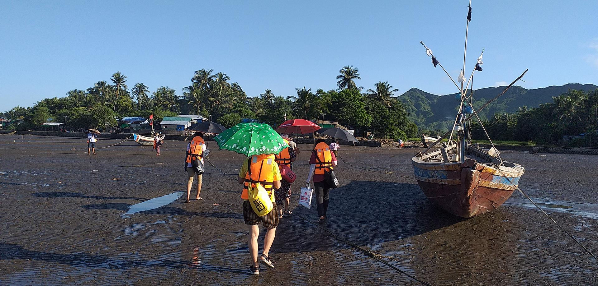 An MSF outreach team walking in from their boat in Central Rakhine